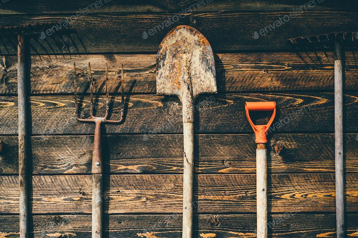 Farm tools in front of wooden old barn. Gardening Equipment