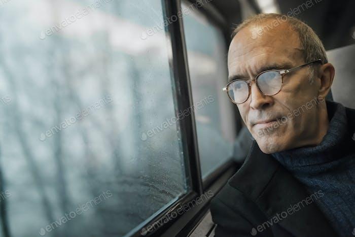 Ein reifer Mann sitzt auf einem Fenstersitz auf einer Zugfahrt und blickt in die Ferne.