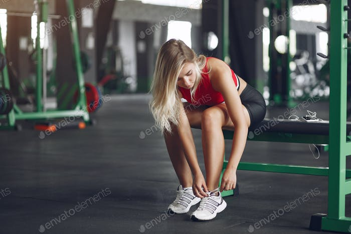 Sports blonde in a sportswear have a rest in a gym
