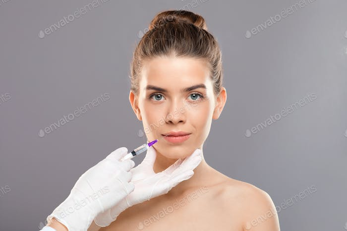 Lip injection for young lady over grey studio background