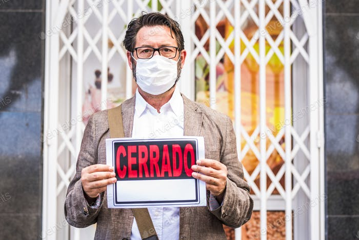 Adult professional businessman with mask and spanish closed sign
