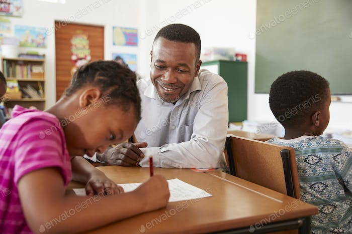 Black male teacher helping elementary school girl in class