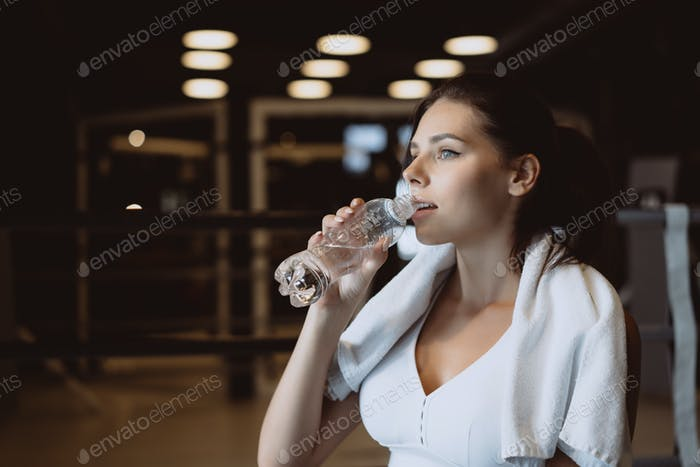 Gorgeous young woman with a towel on her shoulders drinking water from a bottle at the gym