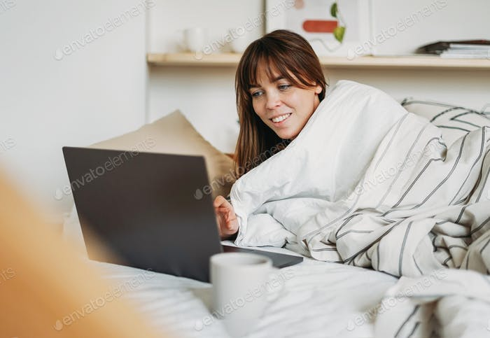 Working young woman freelancer in casual clothes with laptop and cup tea wake up in bed at home
