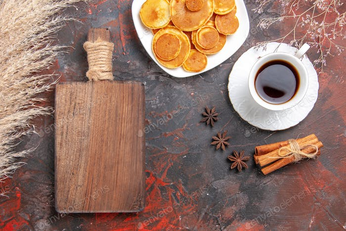 Brown cutting board pancakes and a cup of tea