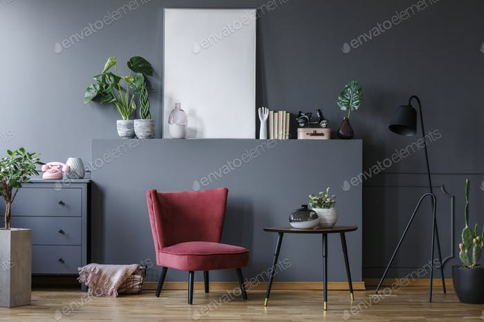 Real photo of a red armchair in a dark living room interior with