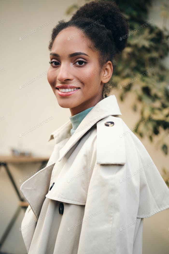 Pretty smiling African American girl in stylish trench coat happily looking in camera on street