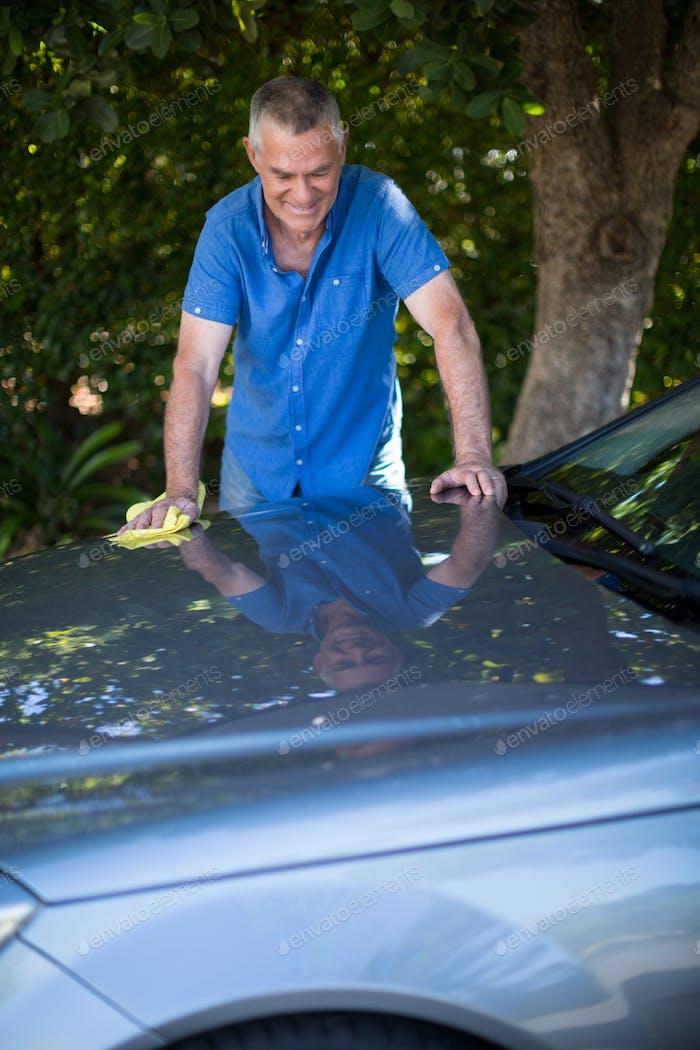 Senior man cleaning car in yard