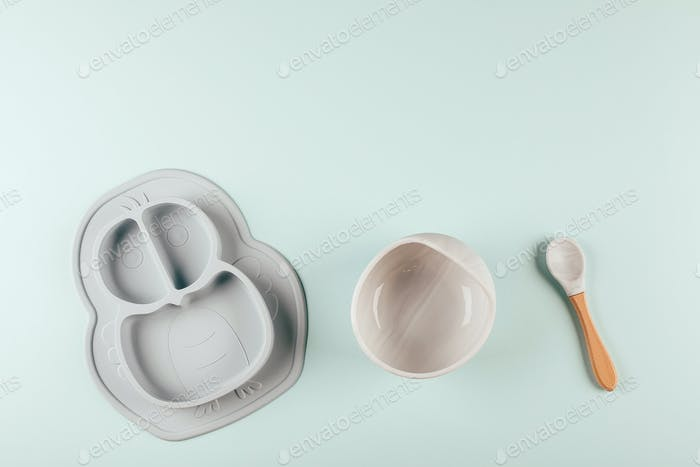 Grey silicone dishware on background. Serving baby, first feeding concept. Flat lay, copy space