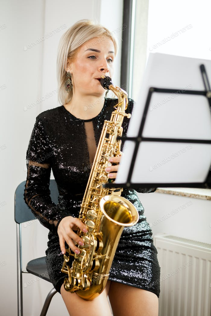 Saxophonist woman with her musical instrument at the window