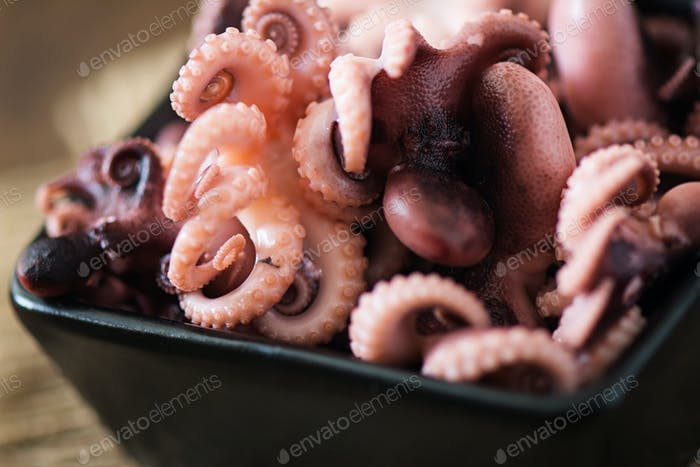 Boiled small octopus on a black bowl
