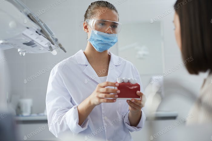 Dental Surgeon Consulting Patient