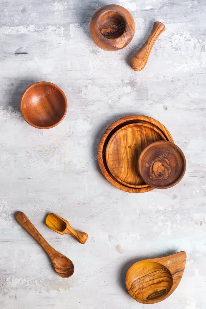 Set of wooden kitchen utensils made from olive wood on stone background, flat lay