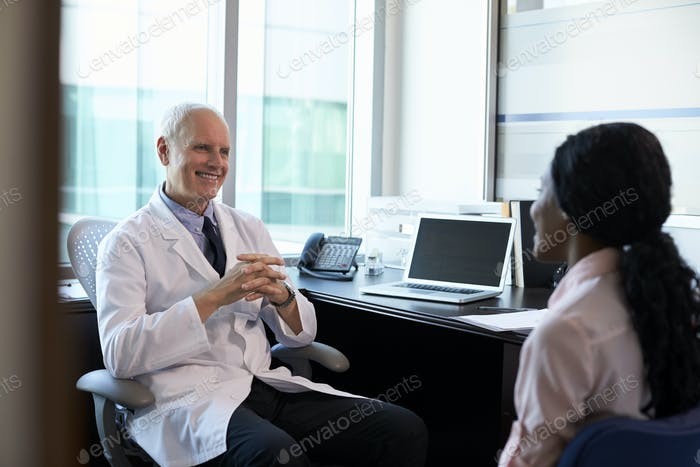 Doctor In Consultation With Female Patient