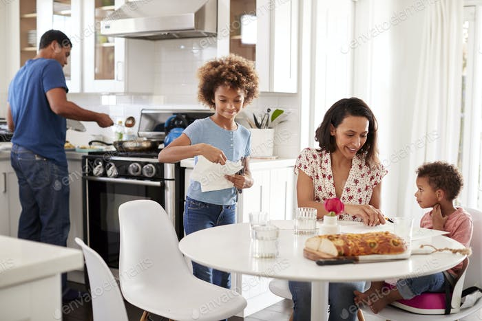 Young mixed race family preparing a meal together in their kitchen