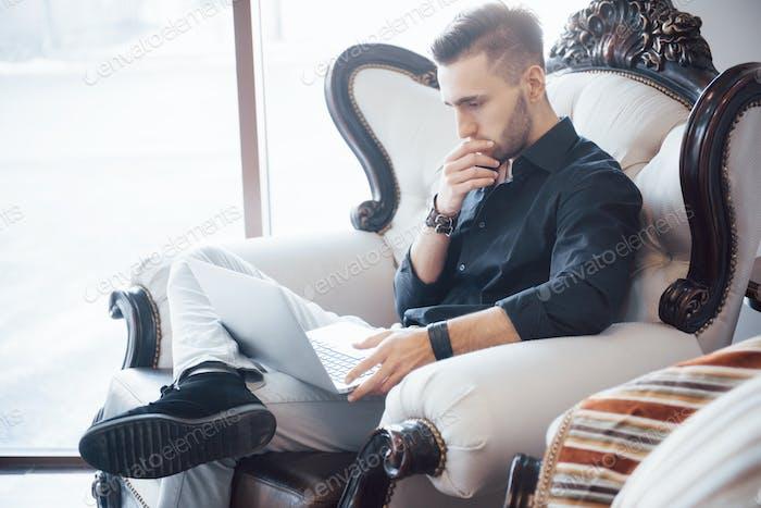 junger Geschäftsmann, der an einem modernen Loft-Büro arbeitet. Mann trägt weißes Hemd
