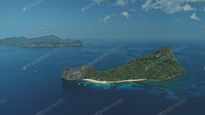 Tropic island at ocean bay aerial view. Boats and ships at harbor. Tropical forest on mountain isle