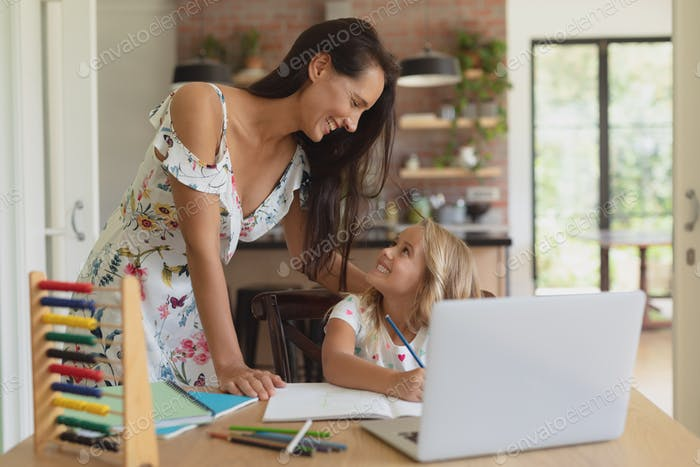 Front view of Caucasian mother helping her daughter with homework in a comfortable home