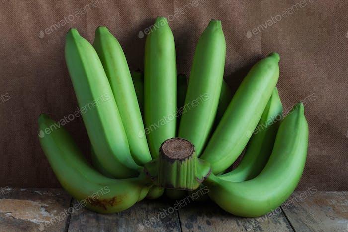 Raw bananas on wood