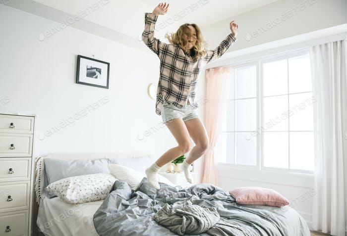 Caucasian girl jumping on bed