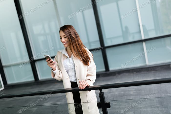 Beautiful and attractive businesswoman texting on cellphone