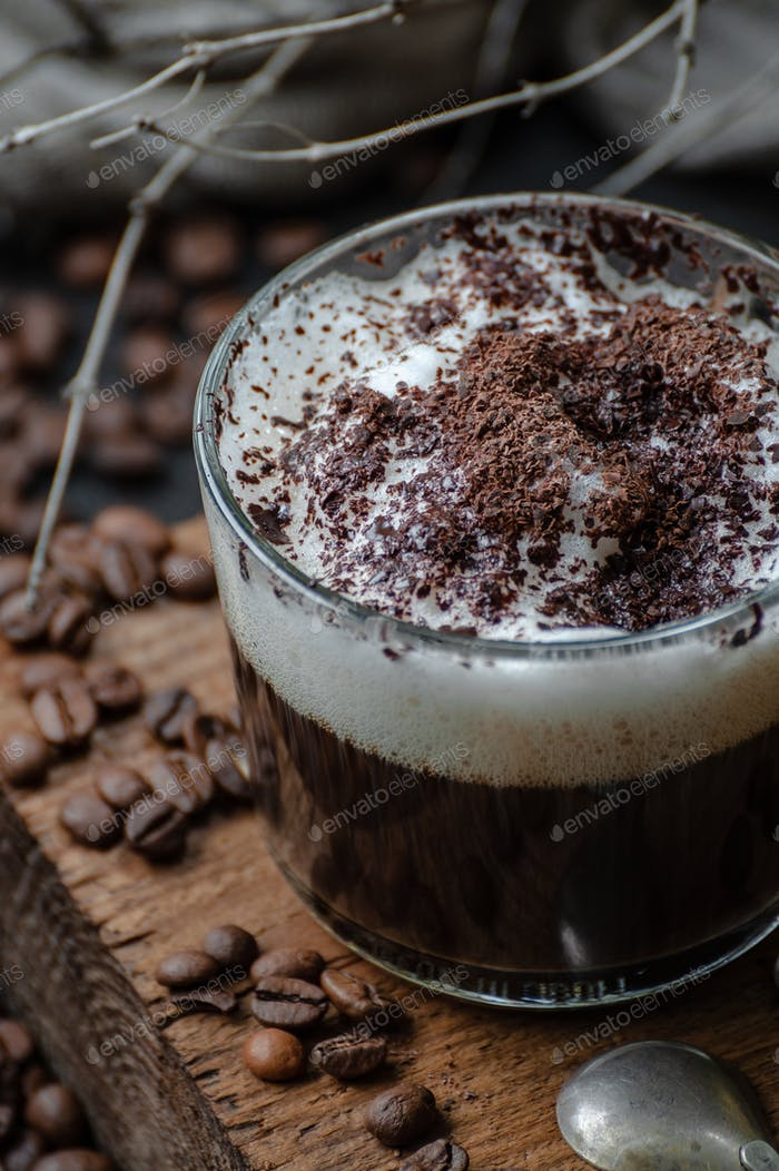 Cappuccino coffee with milk foam and chocolate on a wooden board