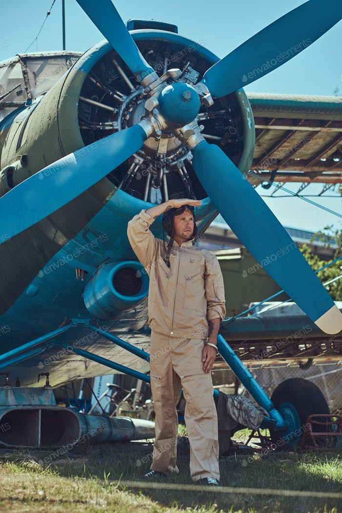 Pilot or mechanic in a full flight gear next to retro military aircraft