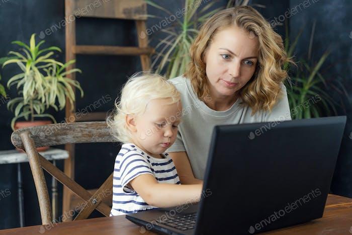 Europäische Familie Mutter und kleine Tochter sitzen am Schreibtisch und schauen auf den Laptop-Bildschirm.