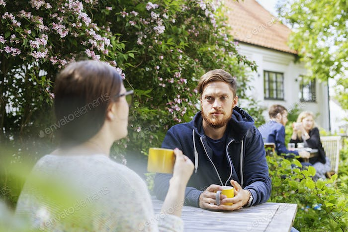 Man looking at friend while holding coffee cup outdoors