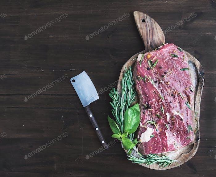 Ein Stück rohes frisches Rindfleisch (Ribeye Steak) mariniert in Gewürzen und