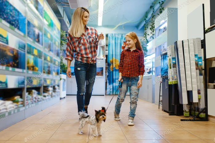 Mother with daughter walking in pet store