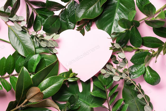 Tropical nature background with green leaves and pink heart shaped paper for copy space. Top view