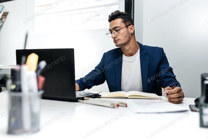 Joven arquitecto de pelo oscuro en gafas y en una chaqueta azul está Trabajo con documentos en el escritorio en