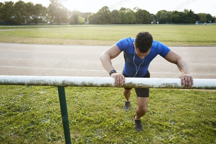 Male athlete stretching at running track, close up