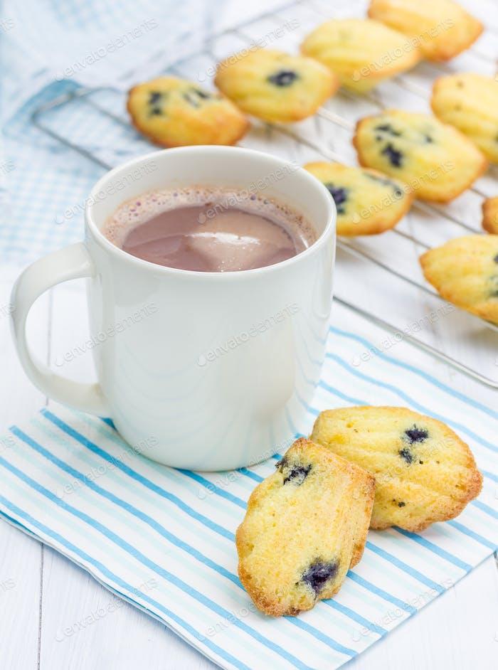 Madeleines mit Heidelbeeren und einer Tasse heiße Schokolade