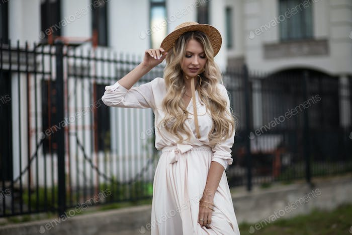 Portrait of beautiful woman with long blonde hair in long white dress walks outside and looks down