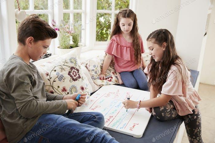 Kinder machen Liste der Aufgaben auf Whiteboard zu Hause