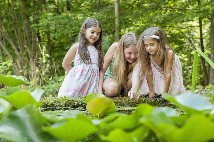 Drei Mädchen spielen draußen.