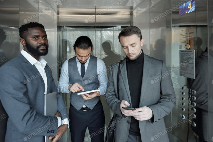 Young African businessman and his colleagues with gadgets moving in elevator