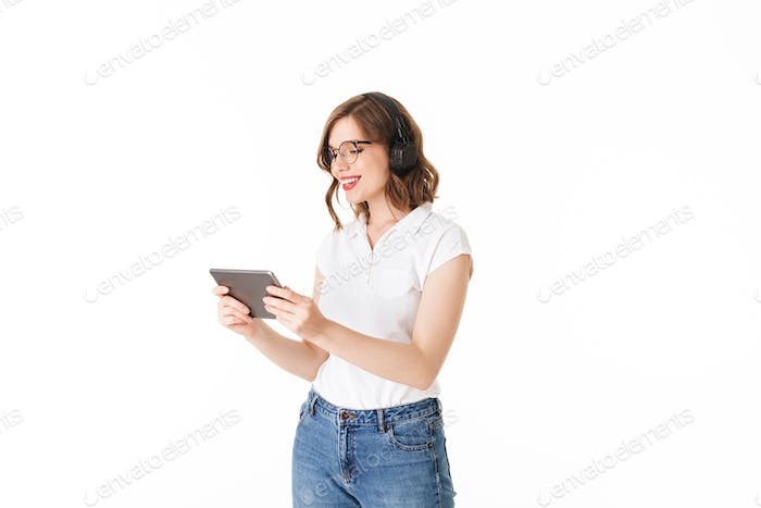 Beautiful smiling lady in eyeglasses and black headphones and happily looking in tablet