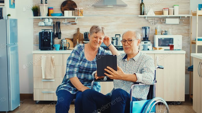 Senior couple on video call with grandchildrens