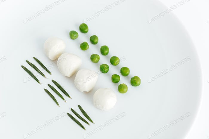 Herbs, green peas and mozzarella on the plate