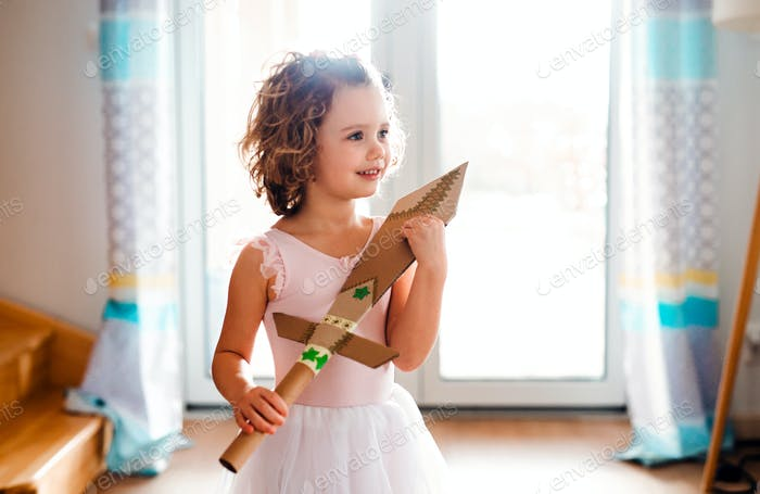 A small girl with a princess dress at home, holding a toy sword.