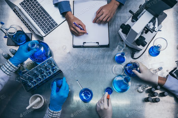 top view workspace in laboratory with microscope, laptop, and laboratory tools