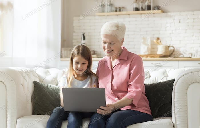 Cheerful mature woman and her granddaughter using laptop together indoors, playing video games or
