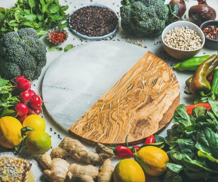Vegetables, beans, grains, greens, fruit, spices over grey background