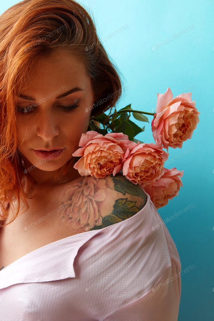 Attractive girl with tattoo on her shoulders and bouquet of coral roses on a blue background, place