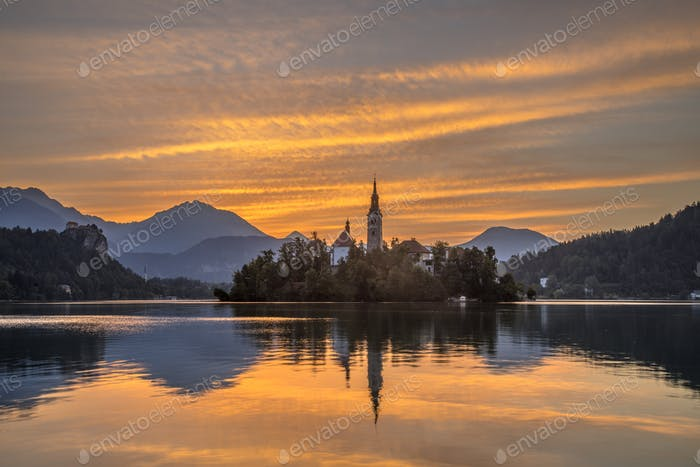 Landscape Lake bled with church under orange morning sky