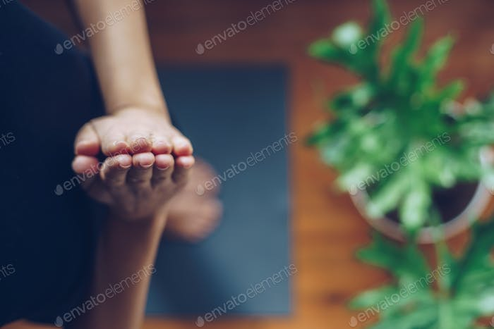 Young woman doing yoga in the morning at her home, top view