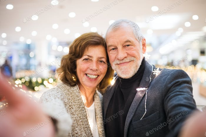 Senior couple taking selfie in shopping center at Christmas time.